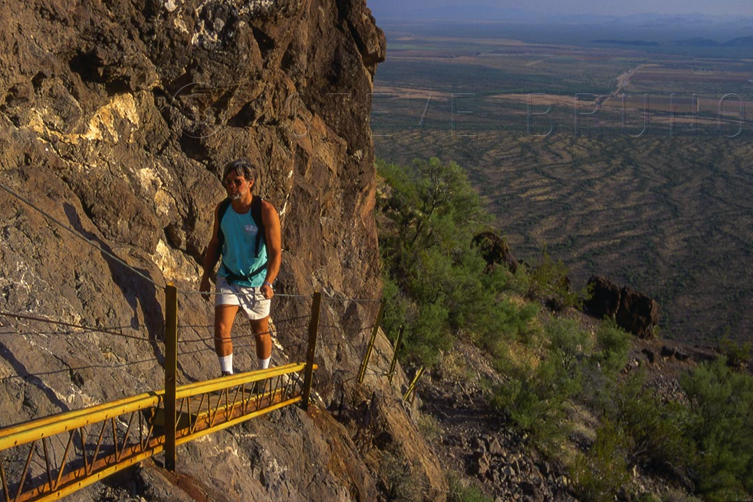Hiker on the built-up portion of the summit trail to Picacho Peak, Arizona by Steve Bruno